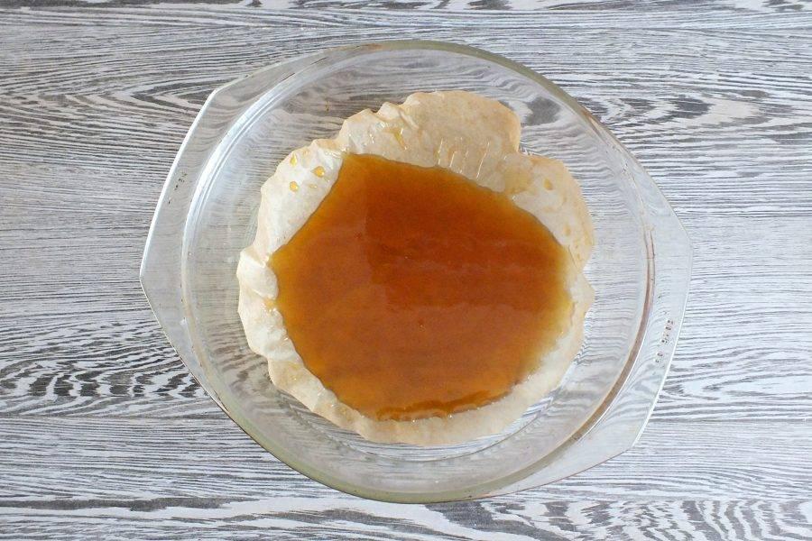 Возьмите форму для выпечки. Застелите ее бумагой для выпечки. Сверху вылейте сливочную карамель.