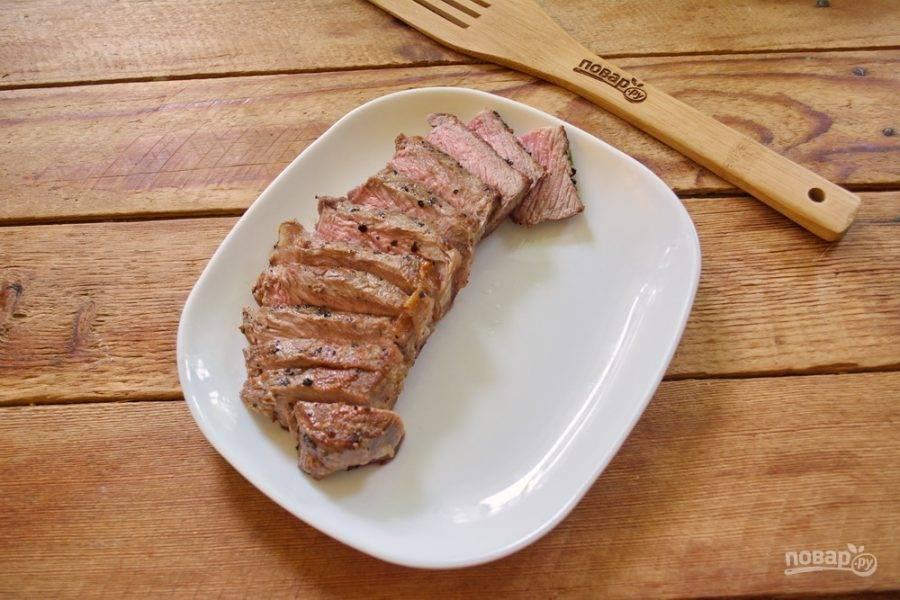 В сковороду влейте немного растительного масла. На очень сильно разогретой сковороде обжарьте стейк со всех сторон. Время обжарки — по 2 минуты с каждой стороны. Еще раз повторюсь: стейк нельзя отбивать молоточком, чтоб мясо стало мягче. Использовать черный молотый перец (порошок) тоже нельзя. Обжаренному стейку дайте отдохнуть (не на сковороде). Спустя 3-5 минут нарежьте на пластинки. Мясо внутри должно быть розовым, а мясной сок — прозрачным.