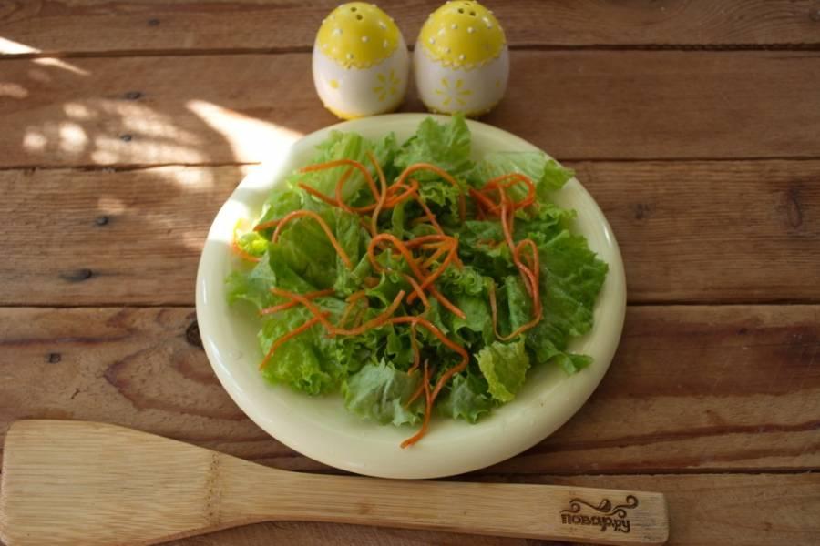 Из маринада вынуть морковь по-корейски. Кусочки морковки разложить на салатные листья.