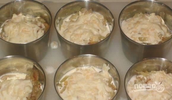 Отварную курицу нарежьте и выложите на лук. В отдельной пиалочке смешайте сливки и плавленый сыр, доведя их до однородности. Полученным соусом залейте содержимое кокотниц.