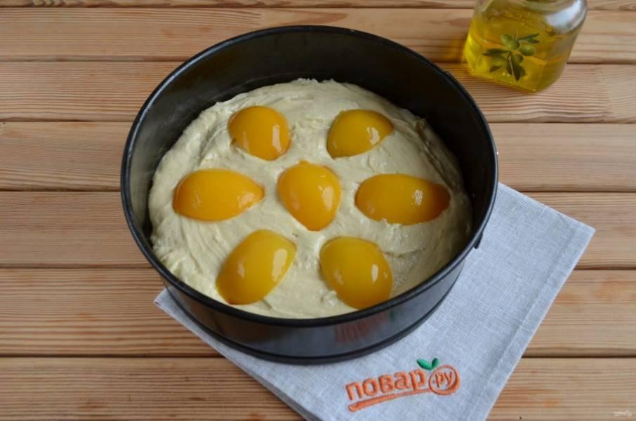 9. Половинки персиков порежьте на пополам. Разложите красиво на пироге, чуть вдавите их в тесто. Разогрейте духовку до 180 градусов. Поставьте пирог на 35 минут.