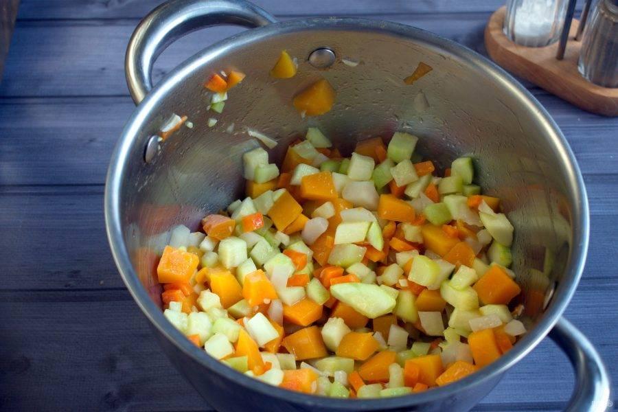 В кастрюле с толстым дном разогрейте масло. Обжарьте овощи в следующем порядке: тыкву и морковь в течение 5 минут,  помешивая; затем добавьте лук и кабачок, готовьте еще 2-3 минуты.