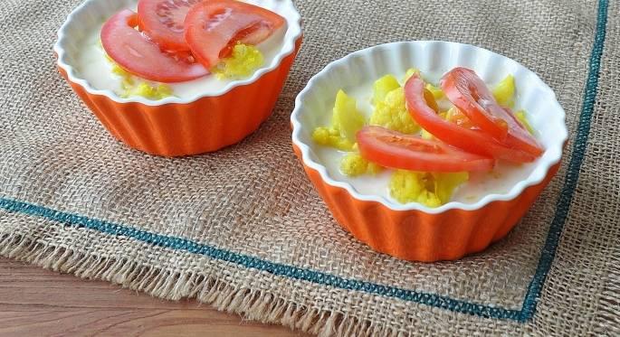 2. Когда соцветия отварятся, дайте им стечь на дуршлаге около нескольких минут. После этого выложите их на дно формочки. Сверху положите нарезанный полу кольцами помидор.