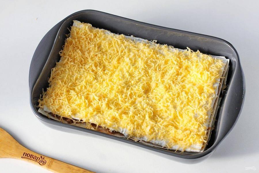 Сверху выложите последний лист лаваша, обильно смажьте его сметаной и посыпьте тертым сыром. Готовьте в духовке при температуре 180-200 градусов около 20 минут.