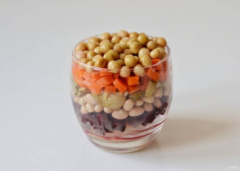 Выложите салат в следующем порядке: картошка, свекла, фасоль, огурцы, морковь. Сверху украсьте горошком. Каждый слой поливайте заправкой.
