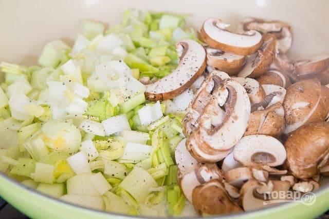 2. Нарежьте слайсами грибы, а лук - кубиками. Выложите ингредиенты в разогретое сливочное масло. Добавьте соль и перец. Жарьте 10 минут.