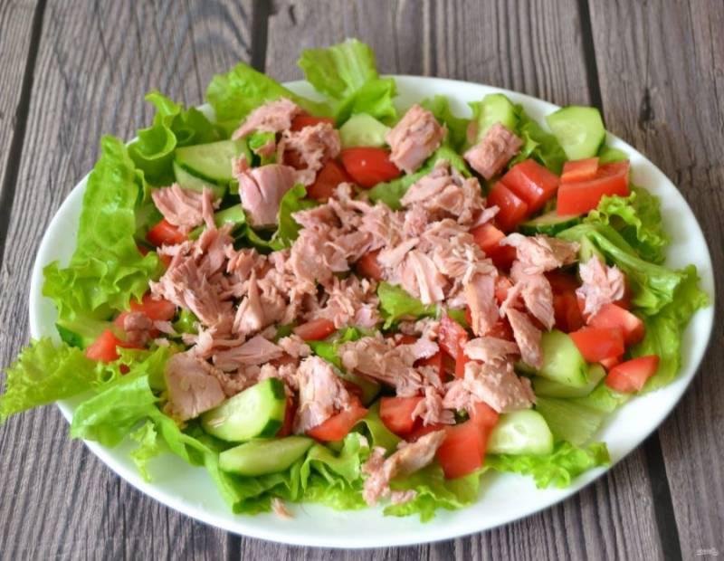 Выложите на салат консервированный тунец, крупные кусочки измельчите.