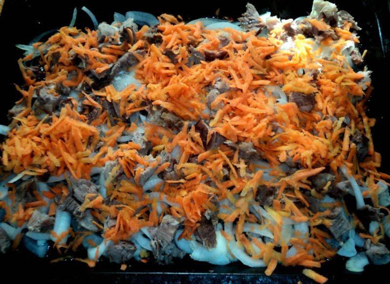 Далее мы смазываем противень небольшим количеством растительного масла и выкладываем на него отваренное и нарезанное на кусочки мясо. На баранину кладем лук и морковь, посыпаем все солью и специями по вкусу.