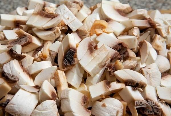 2. Пока обжаривается лук, вымойте, обсушите и нарежьте грибы.