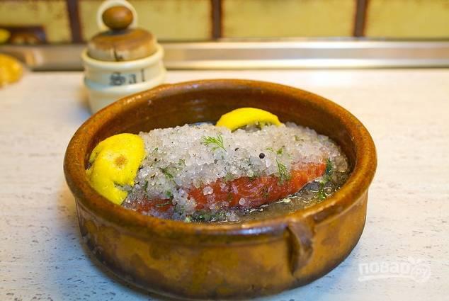 Отправьте рыбу в холодильник минимум на 12 часов. Когда начнет выделяться жидкость, добавьте в емкость две дольки лимона для аромата.