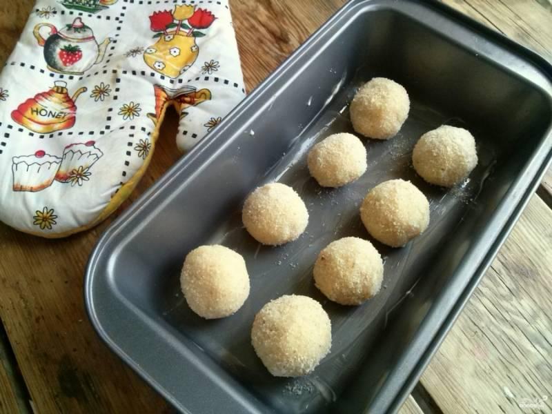 Разогрейте духовку до 180 градусов. Смажьте противень или жаропрочную форму сливочным маслом, выложите на него шарики.