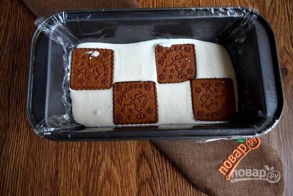 Форму объемом 1,1 л застелите пищевой пленкой. Налейте взбитую смесь на дно формы. Выложите 1 слой печенья, сверху — немного смеси. И так выкладывайте все ингредиенты, чередуя слоями. Поставьте форму в холодильник на 2-3 часа, можно на ночь.