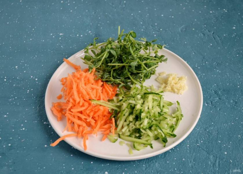 Огурец, чеснок и морковь натрите на терке. Ростки гороха порвите руками.