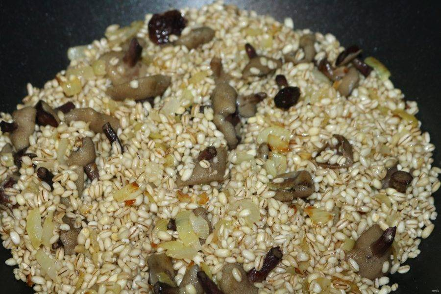 Крупу хорошо промойте, добавьте к грибам и слегка обжарьте. Затем добавьте вино, дайте ему полностью выпариться, постоянно помешивая.