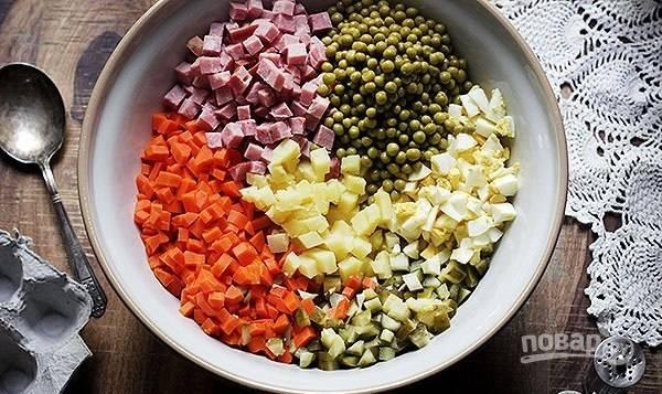 2.Очистите морковь, картофель и яйца, нарежьте маленькими кубиками. Соленые огурцы и колбасу также нарежьте кубиками. Выложите все продукты в большую миску, добавьте консервированный горошек.