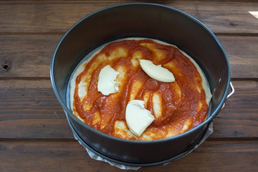 Тесто смазать томатным соусом. Тонкими пластинками нарезать сливочное масло и выложить поверх томатного соуса.