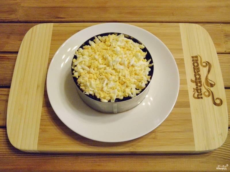 Последний слой салата - тёртые вареные яйца. Утрамбуйте осторожно вилочкой. Снимите сервировочное кольцо при помощи пресса.