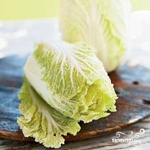 1.Помойте и разберите пекинскую капусту на листки. Срежьте мягкую зелень листов – сейчас вам понадобится только белая плотная часть капусты.