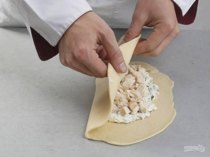 Готовое тесто разделите на 2 части. Каждую раскатайте в круг. Выложите на одну половину начинку. Добавьте филе. Свободные края смажьте взбитым белком, а потом слепите их.