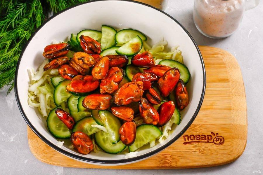 Выложите на огуречную нарезку остывшие мидии в соевом соусе. Заправлять салат ничем не нужно, в соусе мидий содержится растительное масло. Аккуратно перемешайте все компоненты в емкости.
