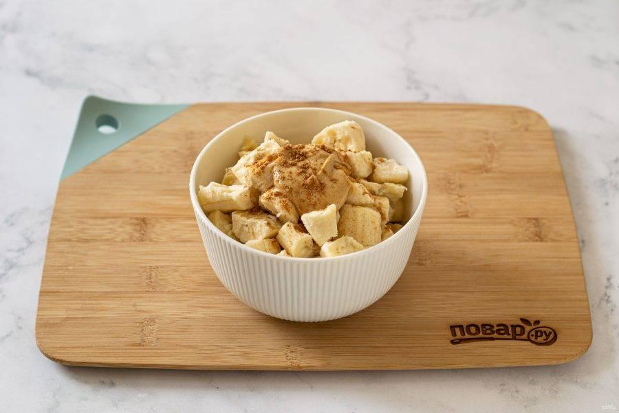 Достаньте бананы, нарежьте на маленькие кусочки. Переложите в глубокую миску, добавьте арахисовую пасту и корицу.