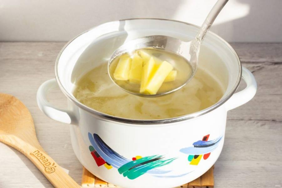 Курицу уберите из бульона и положите картофель, нарезанный брусочками. Варите после закипания на среднем огне 5 минут.