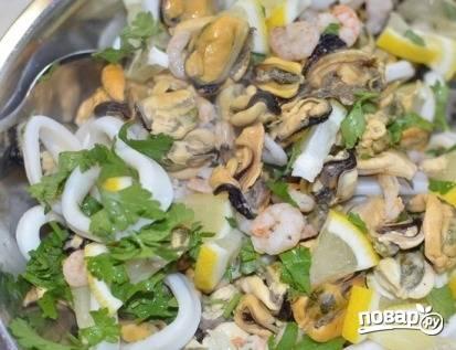 Смешиваем готовые кальмары, мидии и креветки с лимоном и петрушкой. Аккуратно все перемешиваем.