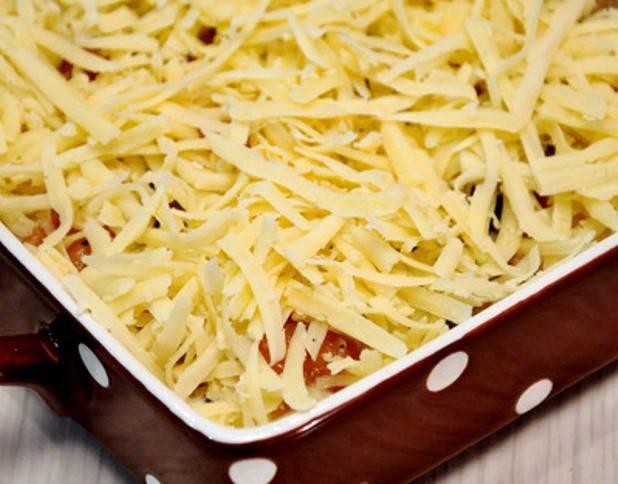 Обильно посыпьте тертым сыром и запеките в духовке в течение 10 минут при 180 градусах.