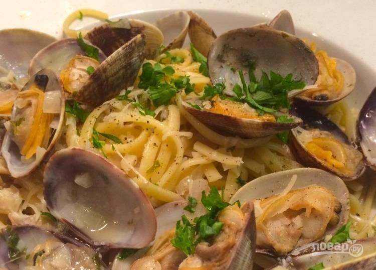 12.Разложите лапшу по тарелкам, добавьте моллюски, украсьте оставшейся петрушкой и подавайте к столу.