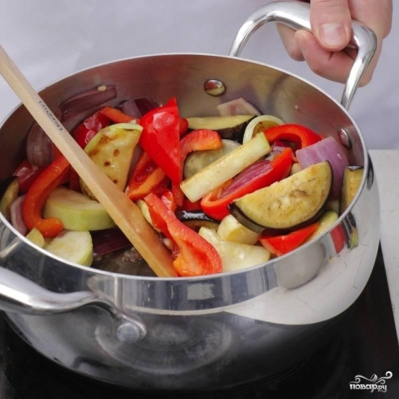 В жаровне разогреть масло, обжарить в нем чеснок в течение 30 секунд. Затем добавляем кабачок и баклажан, жарим еще 4-5 минут на среднем огне, после чего добавляем перцы и лук и готовим еще 4 минуты.