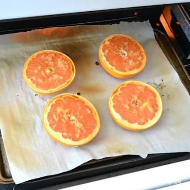 Выкладываем половинки грейпфрута на противень, застланный пергаментной бумагой для выпечки.