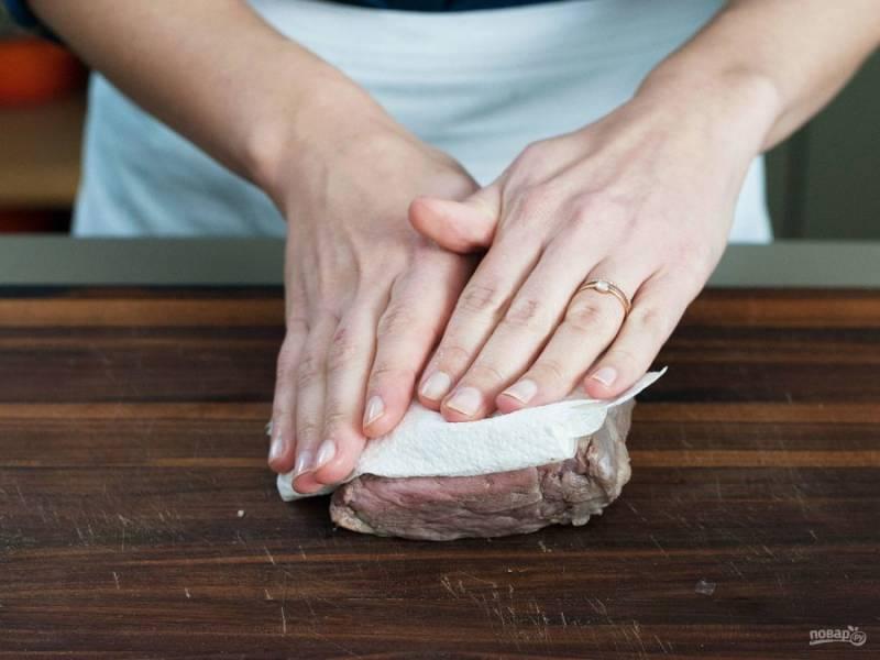 Тем временем готовую телятину промокните от влаги. Смажьте вырезку солью и перцем.
