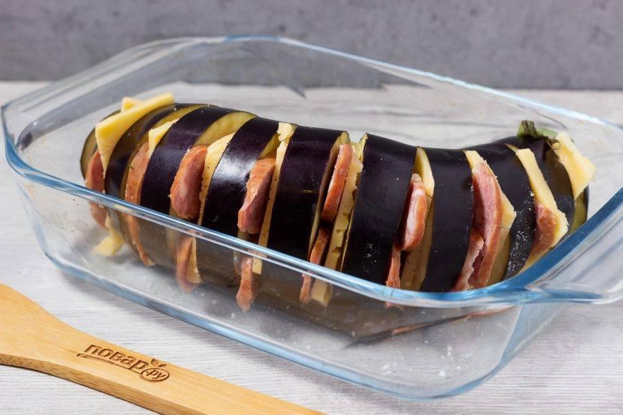Аккуратно разложите в разрезы тонкие пластины сыра и колбасы.