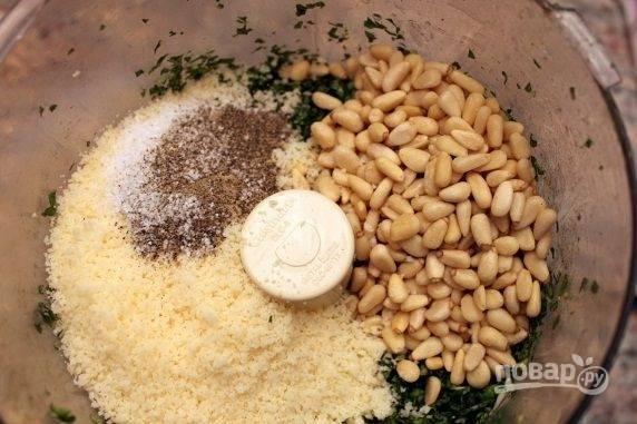 Соедините в чаше блендера базилик, орешки, соль, перец. Мелко натрите пармезан.