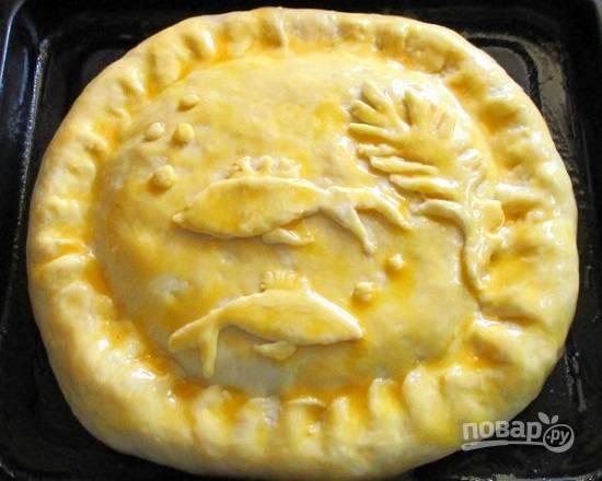 Из оставшегося теста вырезаем украшения для пирога. Смазываем пирог желтком.