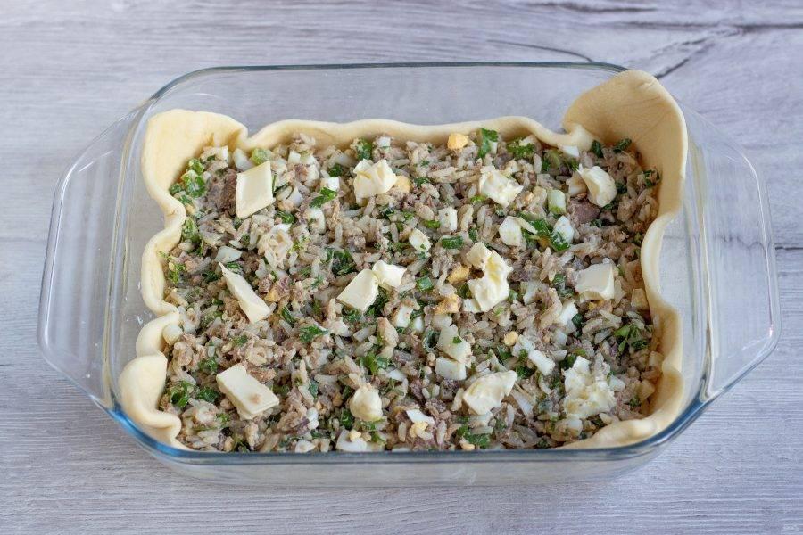 Начинку переложите на тесто. И сверху положите небольшие кусочки сливочного масла, оно даст сочность начинке.
