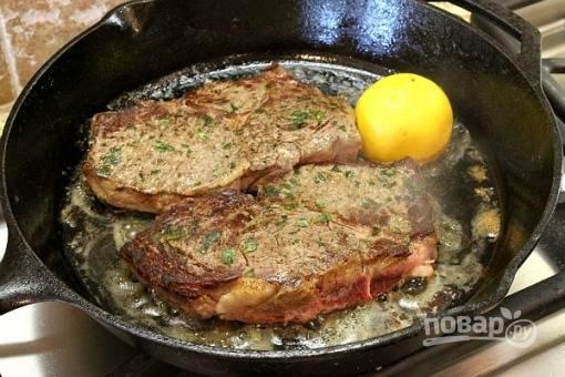 Затем обжариваем стейки по 3-4 минуты с обеих сторон на большом огне на смеси оливкового и сливочного масла. Когда стейки будут почти готовы, добавьте на сковороду половинку лимона.