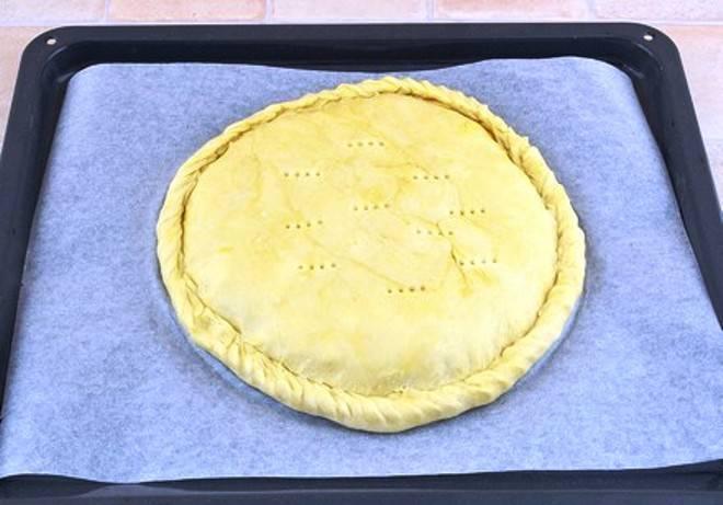 На начинку положите порезанное тонкими пластинками сливочное масло и накройте все вторым коржом. Защипните края теста, сделайте несколько проколов по поверхности с помощью вилки. Разогрейте духовку до 200 градусов и выпекайте пирог в течение 40 минут. Сразу можно подать на стол.