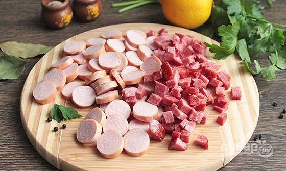 Колбасу и сосиски почистите и нарежьте.