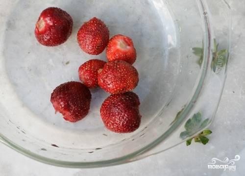 Ягоды клубники замочите в воде, чтобы тщательно смыть с нее всю грязь. Для приготовления пирога лучше использовать клубнику прямо с грядки, так как она самая вкусная и ароматная. Но если такой нет, то можно брать и замороженную или ягоды из варенья. Нарежьте ягоды на произвольные кусочки, но не слишком мелко.