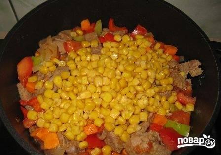 Когда мясо с овощами закипит, добавим консервированную кукурузу. Тушим на небольшом огне минут 7-8. Если в блюде мало сока можно добавить немножко воды.
