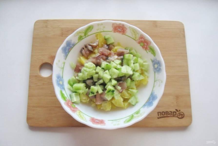 Свежий огурец очистите, нарежьте мелкими кубиками. Добавьте в салат.