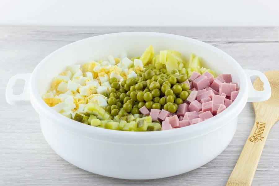Картофель, яйца, колбасу и огурцы нарежьте небольшими кубиками. Соедините всё в миске вместе с горошком.