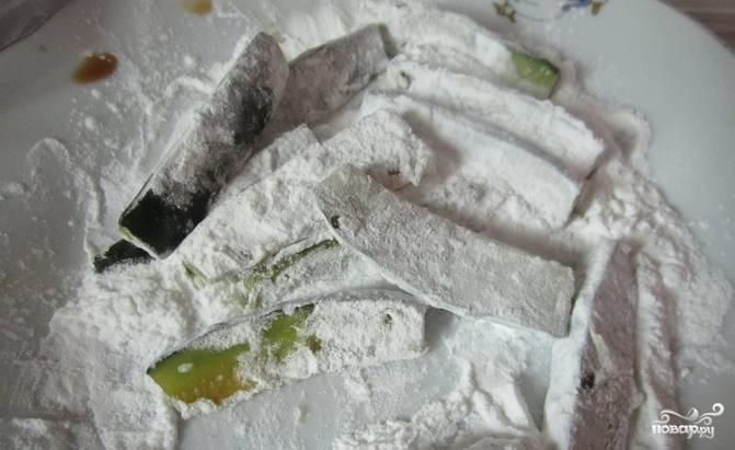 2.Овощ обваляйте в крахмале. Возьмите глубокую сковороду и раскалите, добавьте растительное масло и разогрейте его. В сковороду опустите порезанный лук, чеснок и имбирь. Постоянно перемешивайте, чтобы не пригорели.