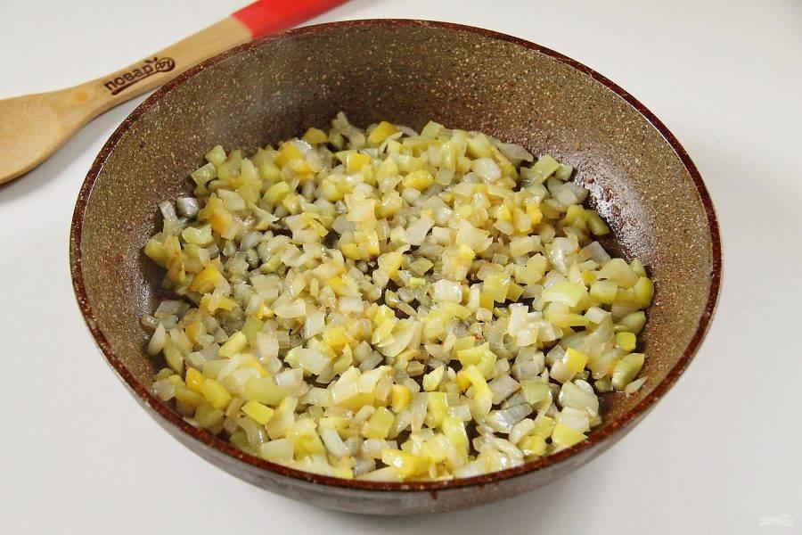 Переложите курицу на тарелку, а на этой же сковороде обжарьте нарезанный кубиками лук и перец.