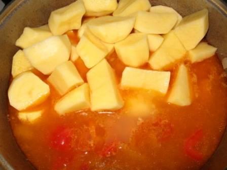 Когда время выйдет, мы выкладываем в казан очищенный и нарезанный крупно картофель.