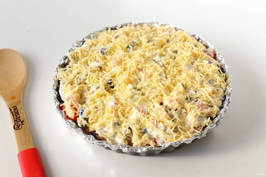 Смажьте овощи сметаной и посыпьте все тертым сыром. Запекайте блюдо в духовке при температуре 180 градусов около 20 минут.
