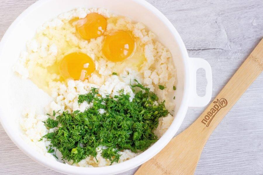 Укроп помойте и нарежьте. Добавьте в творог сахар, соль, яйца и укроп. Перемешайте.