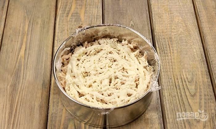 Филе курицы отварите в течение 20-25 минут в солёной воде. Затем остудите его и мелко нашинкуйте. Уложите курицу поверх грибов, смазав её майонезом.