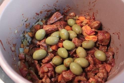 """Перекладываем телятину и помидоры с чесноком в чашу к остальным ингредиентам, добавляем оливки, наливаем в чашу вино и перемешиваем все. Включаем режим """"Тушение"""" и готовим мясо с овощами пол часа. По истечении времени открываем крышку, выливаем в чашу оставшееся вино, солим и перчим все по вкусу и готовим телятину на этом же режиму еще 1,5 часа."""